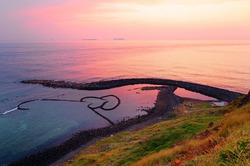 Sunrise over the Double-Heart Stacked Stones or Twin-Heart Fish Trap, which is a fishing weir and a popular tourist attraction in Cimei, Penghu, Taiwan, with golden sunlight reflected on the seawater