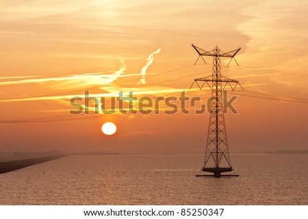 Sunrise over the Dutch sea with the silhouette of an electricity pylon