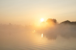 Sunrise over the foggy lake with the reflection of sun and trees in the water. Early fresh morning landscape. Mist on the water, forest silhouettes and the rays of the rising sun.