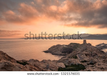 Sunrise over the Genoese tower at La Pietra rock in L'Ile Rousse in the Balagne region of Corsica with the hills of the Desert des Agriates in the distance