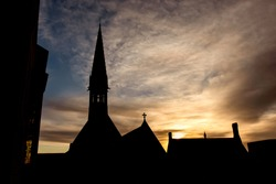 Sunrise over the Harrow School with silhouette of Harrow School Chapel and Vaughan Library, England