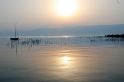 Sunrise over the lake. Boat floating on the calm water under amazing sunset.