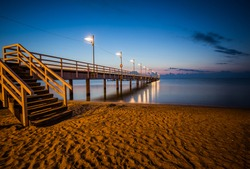 Sunrise over the pier in Mechelinki. Summer seascape background