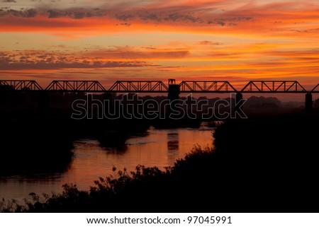 Sunrise over the Sabi River, Kruger National Park, South Africa. The railway bridge at Skukuza Camp