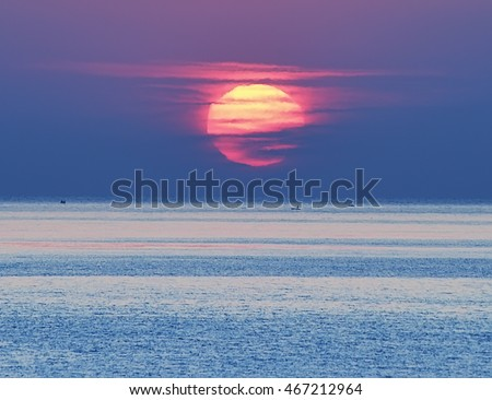 sunrise over the sea. A huge bright red sun emerges from the sea. in the distance small boat on the horizon. Reflected red light on the water.  #467212964