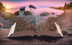 Sunrise over the sea bay with colorful pebble beach on the pages of an open magical book. Majestic nature. Travel concept.