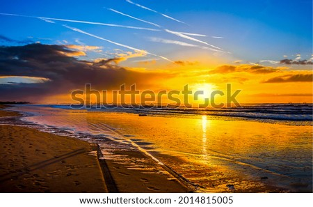 Sunrise over the sea beach with chemtrails. Sunrise beach landscape. Sunrise on the beach