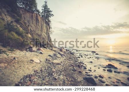 Sunrise over the sea. Beautiful long exposure landscape of rocky seashore. Vintage photo of Gdynia Orlowo.