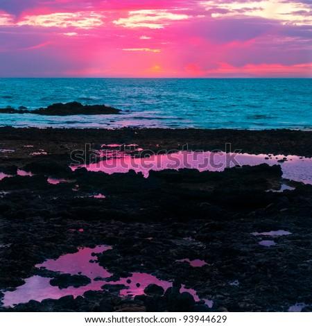 Sunrise over the sea on basalt volcanic shore - stock photo