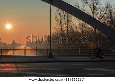 """Sunrise over the waterway """"Teltowkanal"""" in Berlin, Germany on a misty morning. You look at an empty road bridge with a bridge arch and a cyclist on the right."""