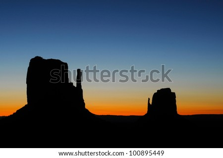 Sunrise painting the sky behind the Mittens at Monument Valley