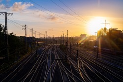 Sunrise panorama with  glowing rails at a Railway Station near Hagen in North rhine westphalia Germany with signals, overhead lines and pylons seen from a bridge