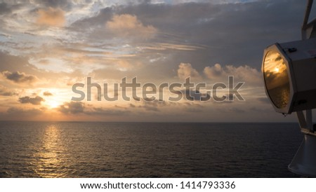 Sunrise reflected on the glass of a searchlight from a boat in the mediterranean sea. Searchlight on bridge wing reflecting a brilliant sunset. Concept of empathy, recognition, be reflected in... #1414793336