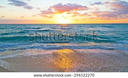 Sunrise reflection on the beach sand. Golden sunrise at ocean beach.
