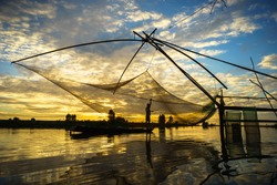 Sunrise scene in Tha La cultivation field with fishing net in Chau Doc, An Giang province, South Vietnam
