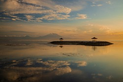 Sunrise seascape. Landscape with mountains and Agung volcano. Traditional gazebos on an artificial island in the ocean. Water reflection. Calm atmosphere. Soft focus. Sanur beach, Bali, Indonesia.