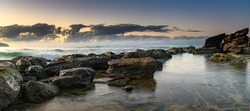 Sunrise seascape panorama with rocks and clouds from Killcare Beach on the Central Coast, NSW, Australia.