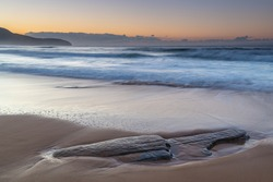 Sunrise seascape with new rocks uncovered and changed landscape from beach erosion at Killcare Beach on the Central Coast, NSW, Australia.