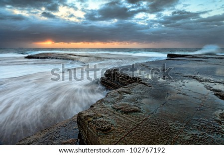 Sunrise seascape with water flowing over rock shelf at Terrigal, near Sydney Australia