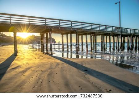 Sunrise shinning through Avila Beach pier on California's Central Coast