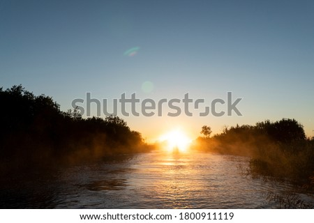 Sunrise sky background. Gold sunrise sky with sky clouds over the lake with fog.Crystal clear water texture. Small waves with water reflection