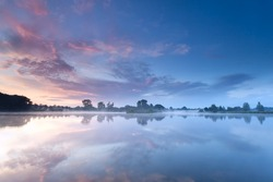 sunrise sky reflected in river during misty morning