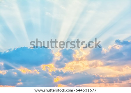 Sunrise sky with sun golden rays breaking through the clouds #644531677