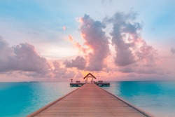 Sunrise sunset bay view, colorful sky and clouds with wooden jetty and over water bungalow, endless horizon. Meditation relaxation tropical background, sea ocean water. Skyscape seascape background