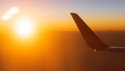 Sunrise view from airplane window seat. Shining sun with lens flare over the wing of plane. Sky at dawn in the background. Soft focus on the wing.
