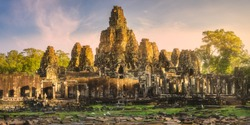 Sunrise view of ancient temple Bayon Angkor complex with stone faces of buddha Siem Reap on sunset, Cambodia