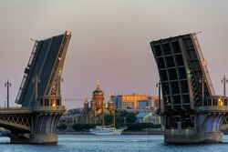 Sunrise view of Church of the assumption of the blessed virgin Mary, 1898, through raised spans of Annunciation (Blagoveshchensky) drawbridge after summer white night. Saint-Petersburg, Russia.