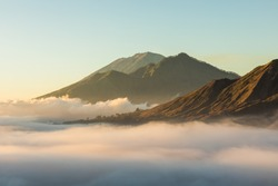 Sunrise view of mount Batur, Abang and Agung volcano in Bali from Pinggan village. Beautiful sunrise and low clouds. Layered minimalist landscape.
