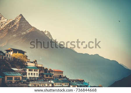 Sunrise view of Namche Bazaar village and Thamserku mountain, Khumbu valley, Nepal. Trekking route to Everest Base Camp, Himalayas. Travel background. Beautiful nature landscape. Retro vintage toning