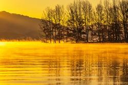 Sunrise view of submerged trees on foggy Daecheongho Lake in autumn near Cheongju-si, South Korea