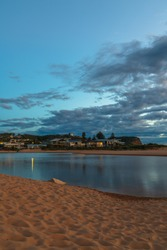 Sunrise waterscape with clouds at the lagoon in Avoca Beach on the Central Coast, NSW, Australia.