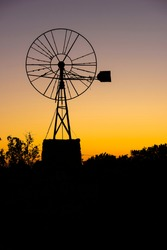 Sunrise with an old backlit windmill, used to draw water from a natural well