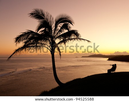Sunrise with couple between two palm trees and looking towards Kilauea lighthouse