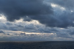 Sunrise with dark clouds and some light breaking thorugh over the Atlantic Ocean near Norway. Nature Background.