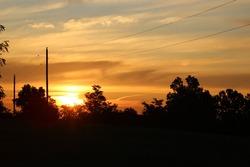 Sunrise with darkened treeline and powerlines