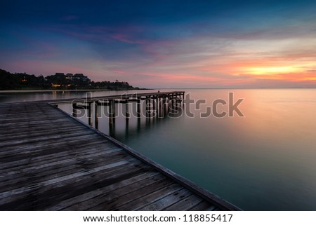 sunrise with dramatic sky and a jetty