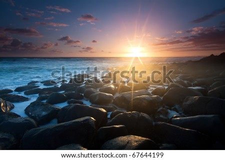 sunrise with interesting full of rocks foreground and nice color clouds in background