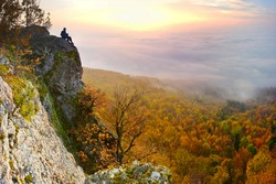 Sunrise with inversion above the deep autumn valley of mountains with small man on the top, who is watching this beautiful scenery