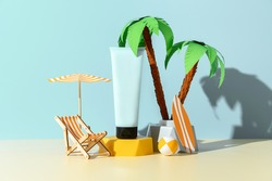 Sunscreen ad template, sunblock tube mockup on podium, decorated with miniature beach chair, palm tree and umbrella. Blue background