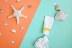 Sunscreen as part of natural composition from shell, stone. Flat lay on turquoise and orange, balance, zero gravity. Sustainable design.