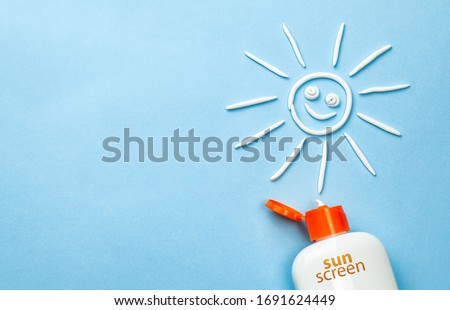 Sunscreen. Cream in the form of sun on blue background with white tube. Stock foto ©