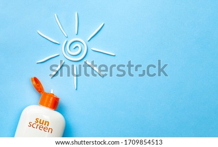 Sunscreen. Cream in the form of sun on blue background with white tube. Copy space for text. Stock foto ©
