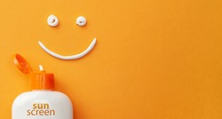 Sunscreen on orange background. Plastic bottle of sun protection and white cream in the shape of Smiley, smiling face.