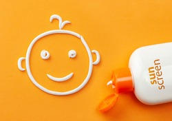 Sunscreen on orange background. Plastic bottle of sun protection and white cream in the shape of a smiling baby face. Cream for kids