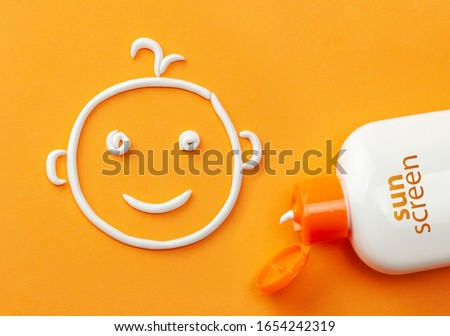 Sunscreen on orange background. Plastic bottle of sun protection and white cream in the shape of a smiling baby face. Cream for kids Stock foto ©