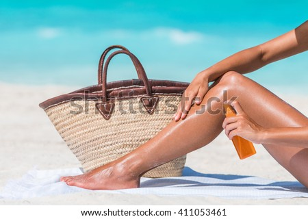 Sunscreen suntan lotion spray bottle woman spraying tanning oil on her leg from bottle. Lady is massaging sunscreen lotion while sunbathing at beach. Unrecognizable model closeup on summer vacation.